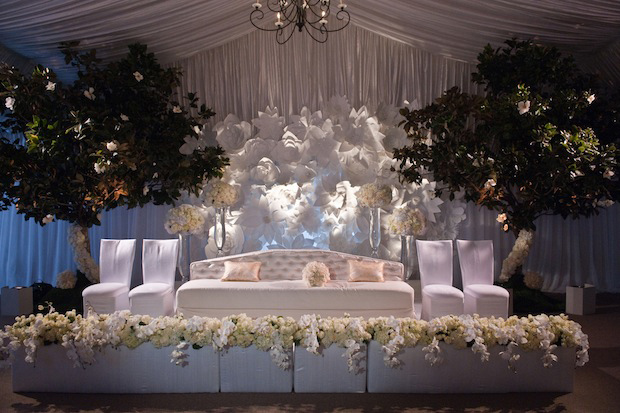 white wedding reception with sheer draping, paper flower wall and white furniture