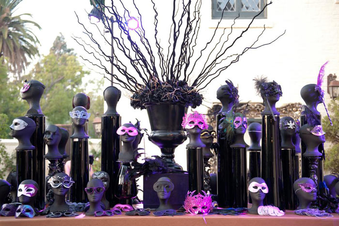 welcome table full of purple masquerade masks