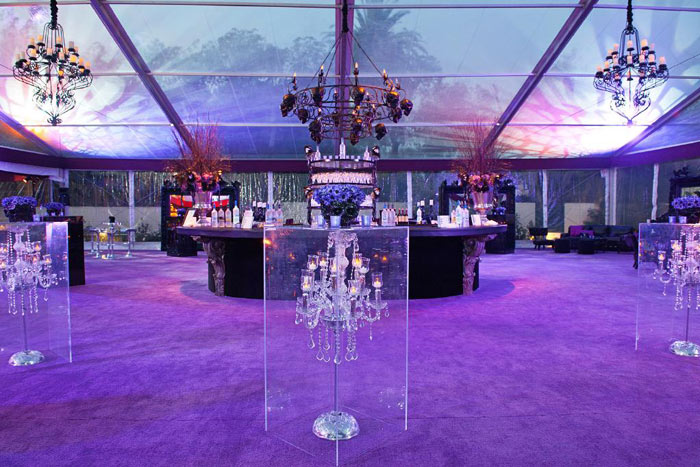 purple carpeted bar area with chandelier encased lucite cocktail tables